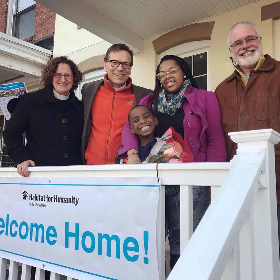 Homeowner stands with volunteers at Home dedication